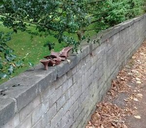 Abandoned high-heeled shoes on front garden wall in Cheltenham