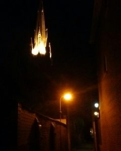 Church steeple glowing at the end of a dark alley