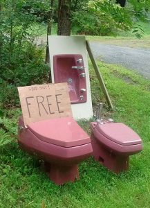 Pink toilet, basin, and bidet set offered free on a lawn