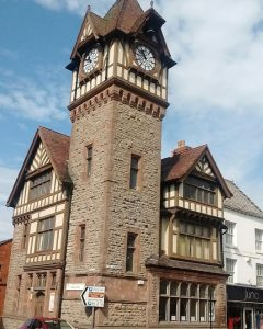 Tudor-sided corner building with gothic-style tower.