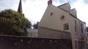 Giant spiders on a house with the words 'Face Your Fear' beside them