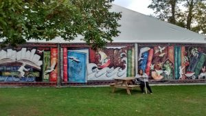A Festival mural depicts travels against a backdrop of giant books.