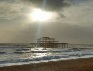 Brighton old pier, sunlight shining through stormclouds