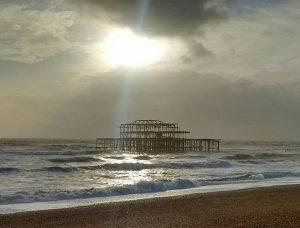 Brighton old pier, sunlight shining through stormclouds
