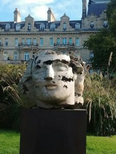Giant face sculpture in front of posh townhouses