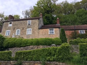 Old stone house with rows of hedge garden
