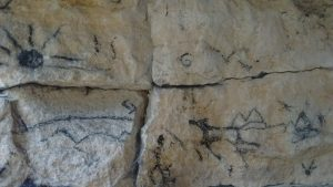 Charcoal sketches of sun and wild animals on the rock face