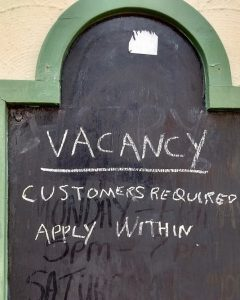 Blackboard outside pub reading: Vacancy, Customers Required...