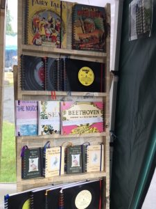 Stand offering notebooks with covers salvaged from old hardbacks and record albums.