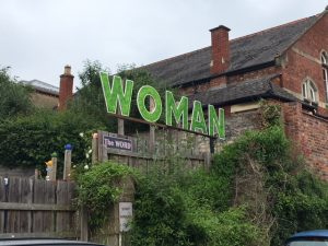 Large letters spelling out Woman, above a label: The Word.