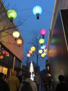 Balloon-shaped lights above the shopping centre with a glowing Christmas tree ahead.