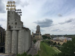 Historic Gold Medal Flour building in the foreground, alongside the river.