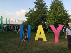 A child climbs around the giant letters spelling HAY in the centre of the festival tents.