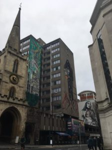 Diverse murals on high rises by a steepled entrance.