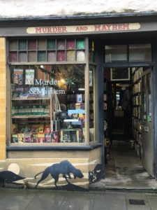 Murder and Mayhem, a uniquely decorated thriller and mystery shop with hounds and a full moon painted below the window.