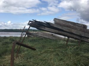 Old exposed boards and rusted iron joins on a grassy bank.