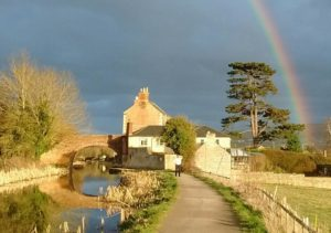 Rainbow over bridge and gatehouse against a stormy sky.