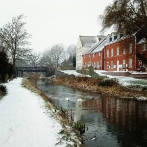 A snowscape with swans swimming down the canal in front of a bridge.
