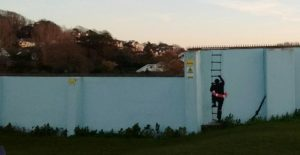 An image of a soldier climbing a ladder painted onto the lido wall in memorium.