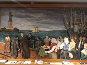 Mural depicting 19th-century immigrants on a ship as they get their first glimpse of the Statue of Liberty