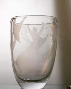 Glass vase etched with a woman hanging laundry in the wind.